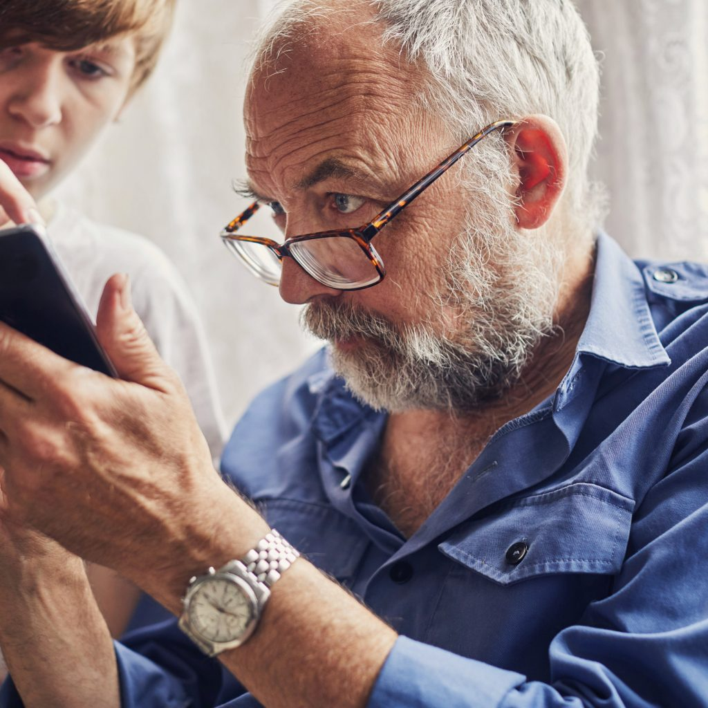 Teenager using a smartphone with his Grandfather