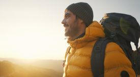 Young man exploring a new mountain area at sunrise. He is traveling alone in a beautiful sunny day.