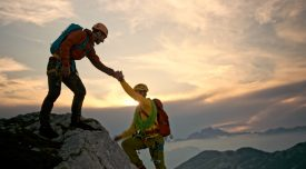 Male rock climber helps his friend get to the mountain top.