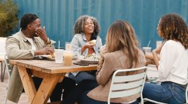 A group of friends laugh together at lunch on an restaurant patio